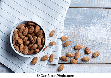 Top view of bowl with handful of almonds on wooden background