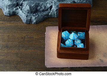 box of blue d & d dice with old paper on table