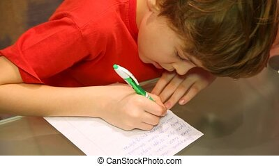 Top view of boy writes something. - Close-up of serious boy...
