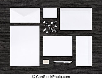 Top view of branding identity mockup with different paper templates for design presentation or portfolio on black table. Includes envelopes, sheets, business card, pen, eraser, clips.