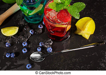 Top view of bright cocktails with mint, ice, berries and carambola on the wooden background. Summer beverages. Copy space.