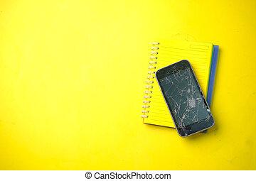 Top view of broken smart phone on yellow background