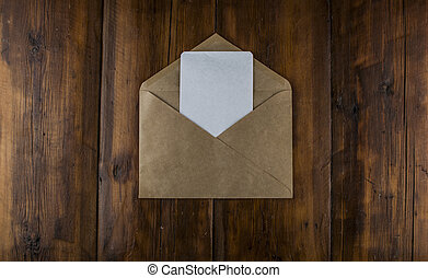 Top view of brown envelope and blank greeting card on wooden background.Copy space
