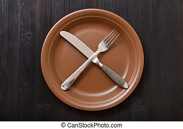 top view of brown plate with cultery on dark table