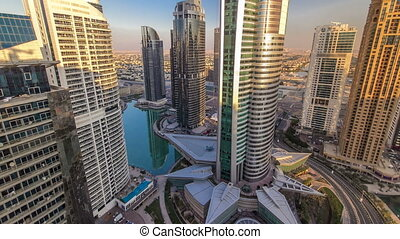 Top view of buildings Jumeirah Lakes Towers with traffic on the road sunset timelapse.