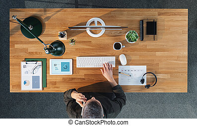 Top view of businessman working on computer at desk with paperwork in home office.