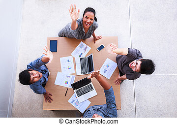 Top view of businessmen and businesswoman celebrate over table in a meeting with copy space at mobile office. Teamwork, diversity, collaboration, success concept