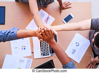 Top view of businessmen and businesswoman standing and stacking hands over table in a meeting with copy space at mobile office. Teamwork, diversity, collaboration concept