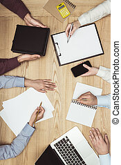 top view of businesspeople on meeting with documents and laptop, digital tablet and smartphone at workplace