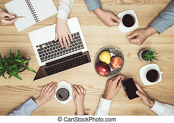 top view of businesspeople on meeting with laptop and coffee at workplace