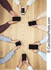 top view of businesspeople on meeting with smartphones with blank screens on wooden tabletop