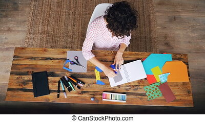 Top view of busy female designer sticking paper figure in...