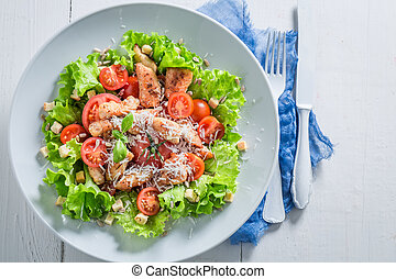 Top view of Caesar salad with chicken, tomatoes and cheese
