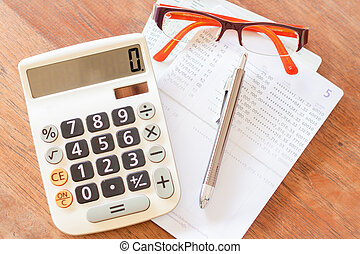 Top view of calculator, pen, eyeglasses and bank account...
