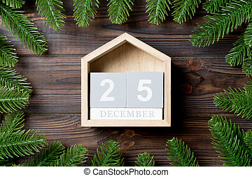 Top view of calendar decorated with a frame made of fir tree on wooden background. The twenty fifth of December. Christmas time concept