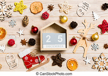 Top view of calendar on Christmas wooden background. The twenty fifth of December. New Year toys and decorations. Holiday concept