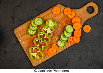 top view of carrot and cucumber and bell pepper slices on wooden cutting board on black background