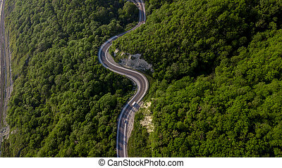 Top view of cars driving on zig zag winding mountain road