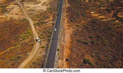 Top view of cars ride along a desert road on Tenerife, Canary Islands, Spain