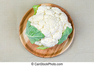 Top view of cauliflower on wooden dish on cloth surface