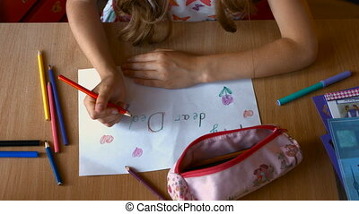 Top view of charming young girl while sitting at the table in nursery and drawing for dear dad