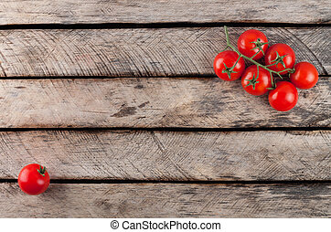 Top view of cherry tomatoes on rustic wooden background with copy space