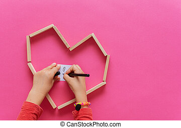 Top view of child's hands drawing on white post it paper placed in a heart