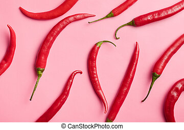 chili peppers on pink background - top view of chili peppers...