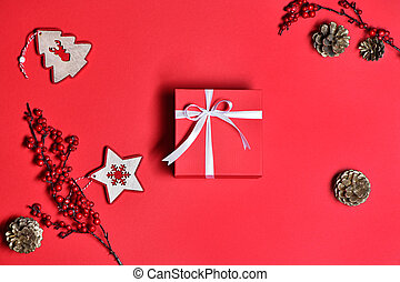 Top view of Christmas gift box with decor on red background