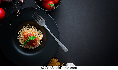 Top view of classic Italian spaghetti pasta with tomato sauce, ingredients and copy space