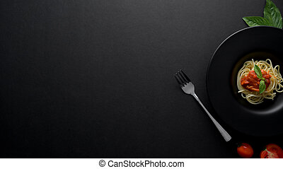 Top view of classic spaghetti pasta with tomato sauce on dark plate and copy space