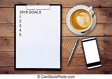 Top view of clipboard written Goals 2019 on wooden background with coffee cup, pen and mobile phone.