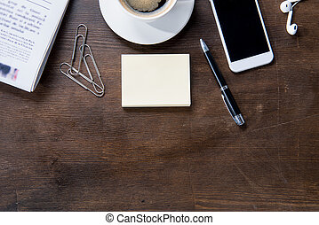 Top view of coffee cup, smartphone and office supplies on wooden table