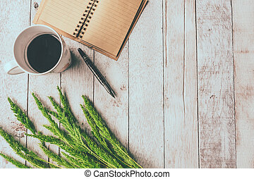 Top view of Coffee cup with blank notebook,pen and paddy rice on white wooden table background, Free space for text, Vintage tone