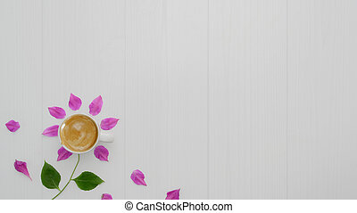 Top view of coffee cup with flower petals, leaves on plank background