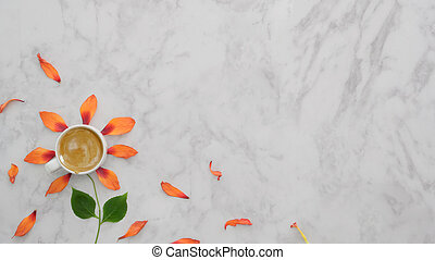 Top view of coffee cup with orange flower petals, leaves on marble background