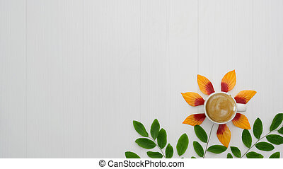 Top view of coffee cup with orange flower petals, leaves on plank background