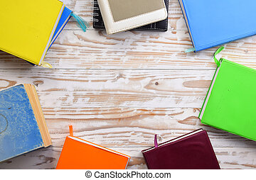 Top view of colorful books on a wooden table.