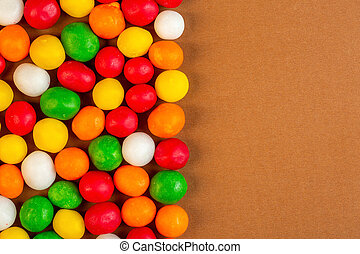 top view of colorful candies with copy space on ochre background