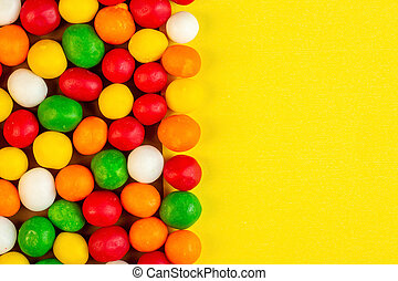 top view of colorful candies with copy space on yellow background