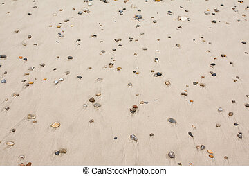 Top view of colorful stones on sand at the beach.