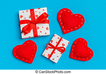 Top view of colorful valentine background made of gift boxes and red textile hearts. Valentine's Day concept