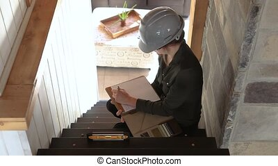 top view of construction inspector woman sitting on the stair and taking notes then she looks to the camera. home interior stairs inspection.