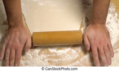 Top view of cook rolling dough with rolling pin - Top view, ...