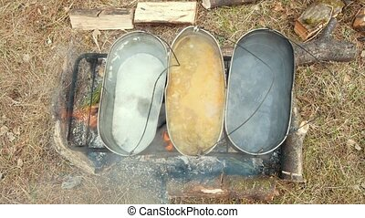 Top view of cooking food in the black iron cauldrons on the...