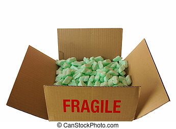 Top view of corrugated cardboard box with the word FRAGILE filled with pieces of green plastic foam used to protect objects inside boxes in a move