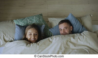 Top view of couple having fun in bed hiding under blanket looking into camera and kissing at home