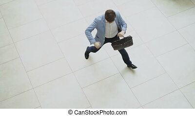 Top view of crazy and funny businessman with briefcase...