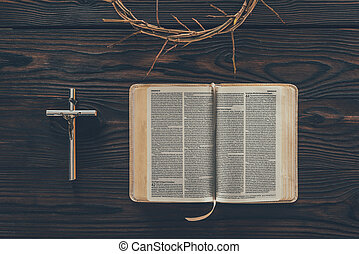 top view of crown of thorns with cross and bible on table