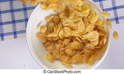 Top view of crunchy corn flakes falling into bowl in slow motion